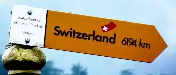 """Swiss hiking footpath sign board which formally and officially declared Khajjiar as """"mini Switzerland""""."""